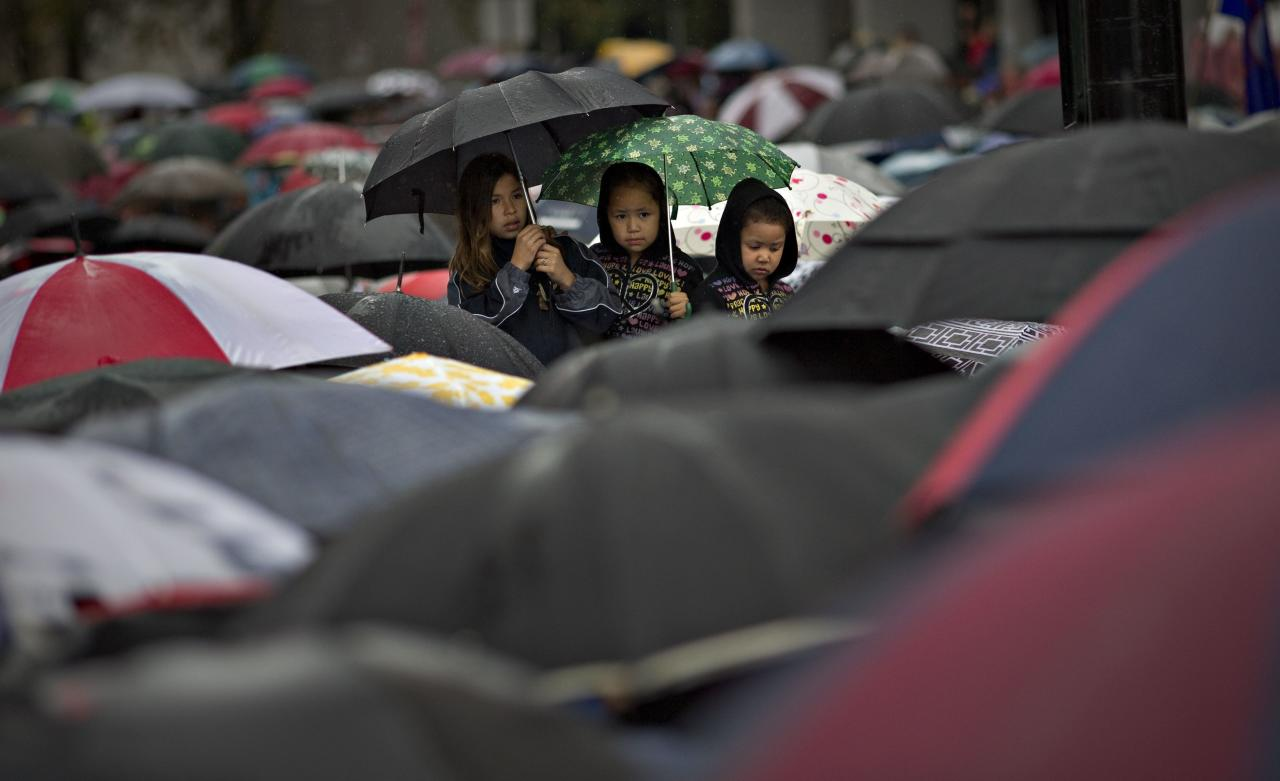 First Nations' children wait in the rain to take part in a Truth and Reconciliation march in Vancouver, British Columbia September 22, 2013. First Nations people, many survivors of the abuse at former Canadian Government Indian Residential Schools, have been meeting for the past week. REUTERS/Andy Clark (CANADA - Tags: POLITICS SOCIETY TPX IMAGES OF THE DAY)