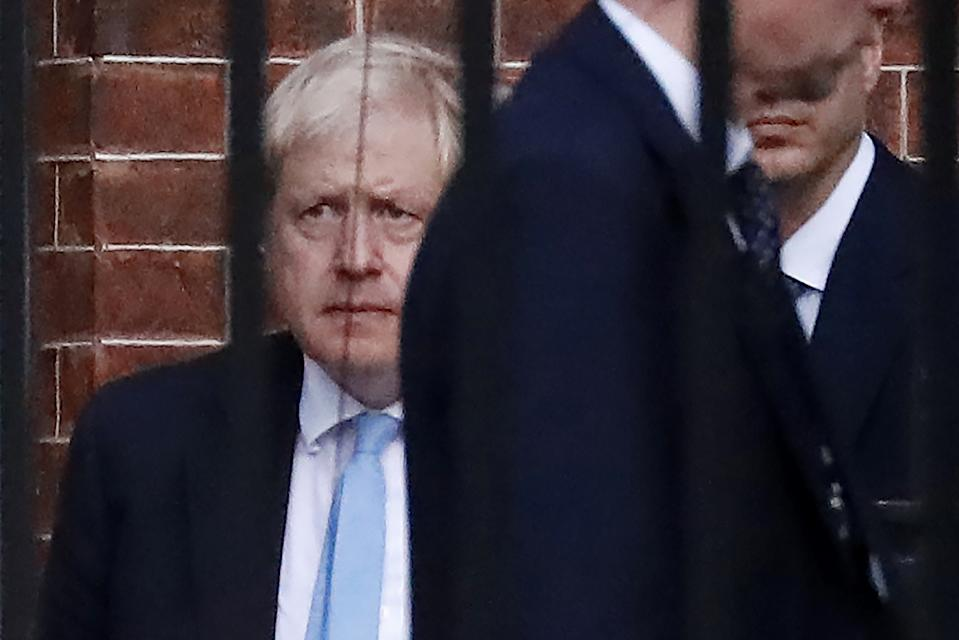 """Britain's Prime Minister Boris Johnson (L) leaves from the rear of 10 Downing Street in central London on October 16, 2019. - British Prime Minister Boris Johnson briefed his ministers and key lawmakers on Wednesday on details of a Brexit deal taking shape in Brussels, while warning an agreement was still """"shrouded in mist"""". (Photo by Tolga AKMEN / AFP) (Photo by TOLGA AKMEN/AFP via Getty Images)"""