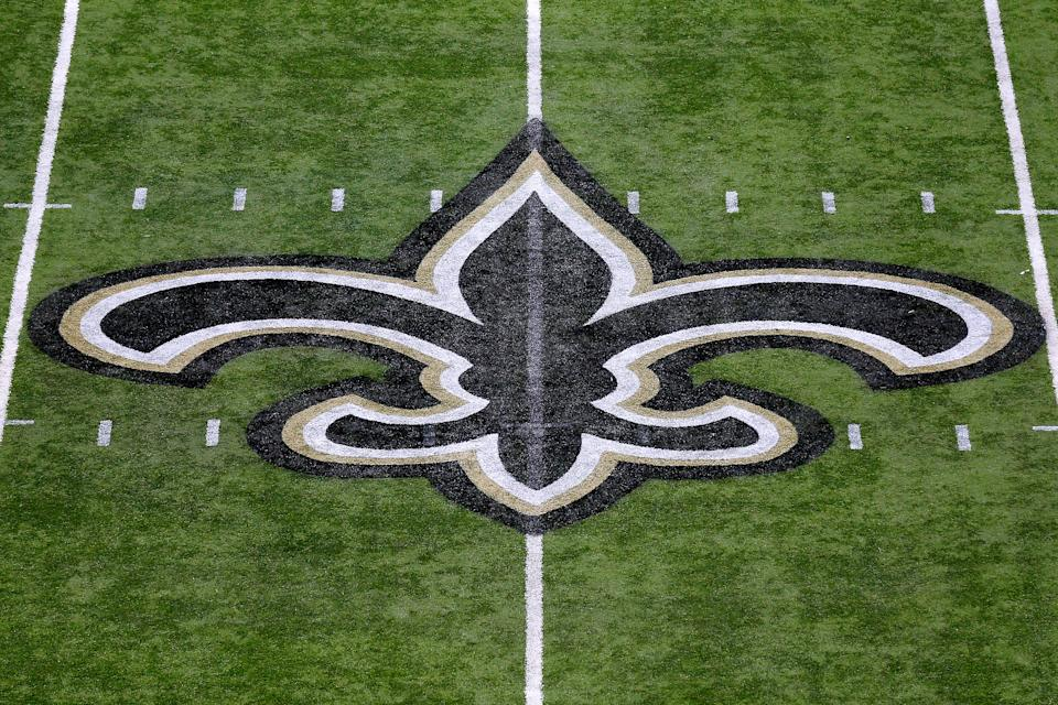 A Saints logo on the field at the Superdome.