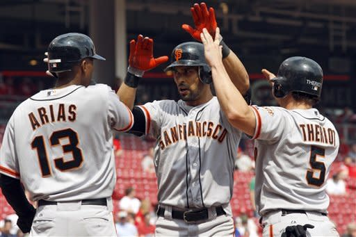 San Francisco Giants' Angel Pagan, center, celebrates with Joaquin Arias (13) and Ryan Theriot (5) after hitting a game-winning, three-run home run off Cincinnati Reds pitcher Sean Marshall during the ninth inning of a baseball game, Thursday, April 26, 2012, in Cincinnati. The Giants won 6-5. (AP Photo/David Kohl)