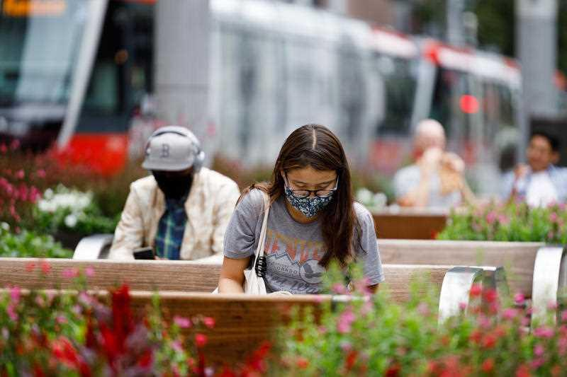 A woman seated on a public bench wears a face mask while reading a book in Sydney.