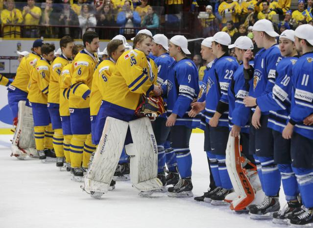Sweden's goalie Oscar Dansk leads his teammates in shaking hands with Finland players after they lost in overtime of their IIHF World Junior Championship gold medal ice hockey game in Malmo, Sweden, January 5, 2014. REUTERS/Alexander Demianchuk (SWEDEN - Tags: SPORT ICE HOCKEY)