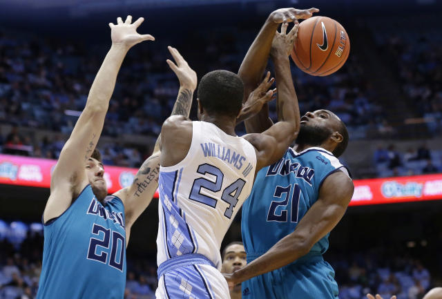 North Carolina's Kenny Williams (24) tries to pass while UNC Wilmington's Matt Elmore (20) and Ty Taylor (21) defend during the first half of an NCAA college basketball game in Chapel Hill, N.C., Wednesday, Dec. 5, 2018. (AP Photo/Gerry Broome)