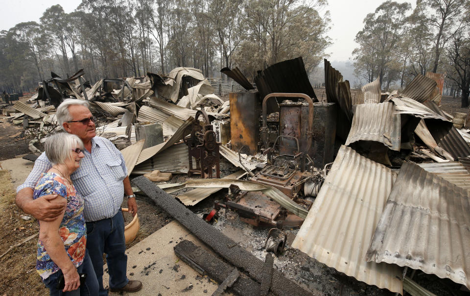 Lyn and Peter Iverson with their burnt out office and shed on their property at Half Chain road, Koorainghat, Monday, November 11, 2019. (AAP Image/Darren Pateman)