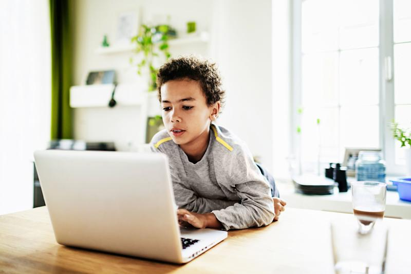 A young boy at home over the weekend using a laptop to do his homework.