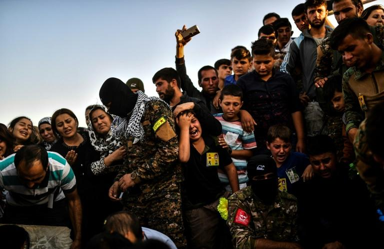 A picture taken on October 14, 2017 in the Kurdish town of Kobane in northern Syria shows people mourning during the funeral of a Kurdish fighter, who was killed in clashes against Islamic State (IS) group fighters in the city of Deir Ezzor