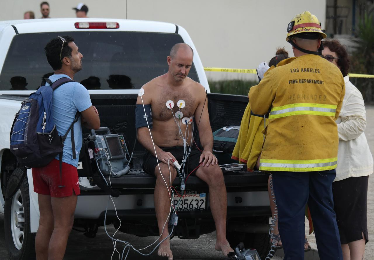 A man is treated by a paramedics after a lightning strike in the water in Venice, California July 27, 2014. As many as nine people were hurt on Sunday after being struck by lightning on Venice Beach in Los Angeles, emergency officials said. REUTERS/Jonathan Alcorn (UNITED STATES - Tags: DISASTER ENVIRONMENT)