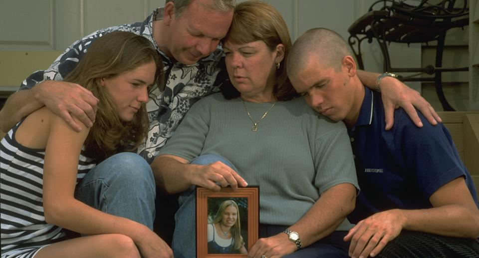 The Smart family (pictured) with a photo of missing woman Kristin Smart.