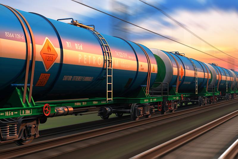 A freight train with petroleum tankers seen at dusk.