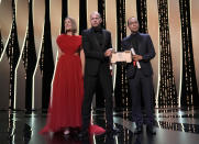 Rosamund Pike, left, poses with Nadav Lapid, center, director of 'Ahed's Knee' and Apichatpong Weerasethakul, director of 'Memoria' as they accept the jury prize during the awards ceremony for the 74th international film festival, Cannes, southern France, Saturday, July 17, 2021. (AP Photo/Vadim Ghirda)