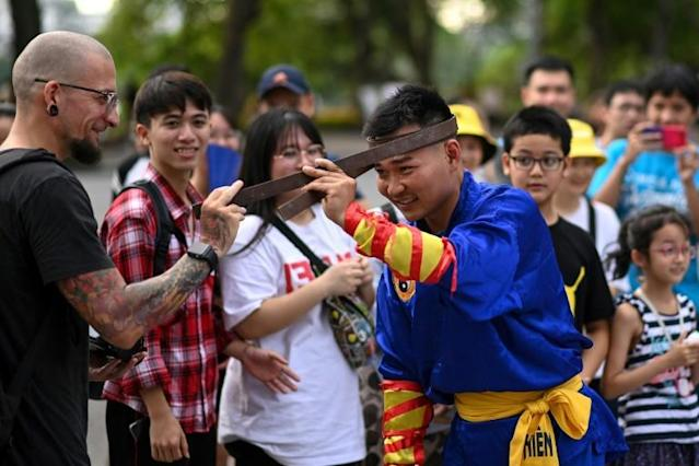 A spectator touches an iron bar bent around the head of a student of the centuries-old martial art of Thien Mon Dao at the Hoan Kiem lake in Hanoi (AFP Photo/Manan VATSYAYANA)