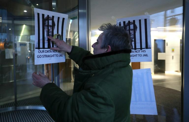 "A man fixes posters depicting Cambridge Analytica's CEO Alexander Nix behind bars, with the slogan ""Our Data Not His. Go Straight To Jail"" to the entrance of the company's offices in central London on March 20, 2018"
