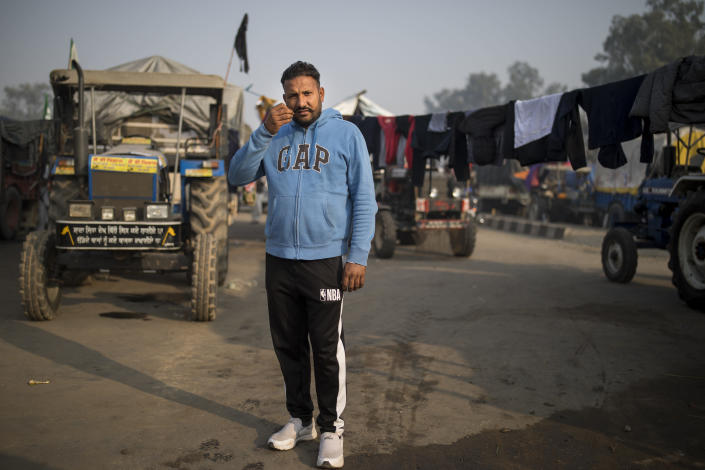 """Hardeep Singh, 42, stands for a photograph next to his tractor trailer parked on a highway as he joins tens of thousands of protesting farmers for a protest against new farm laws at the Delhi-Haryana state border, India, Tuesday, Dec. 1, 2020. The protests started in September but drew nationwide attention last week when the farmers marched from northern Punjab and Haryana, two of India's largest agricultural states. Their rallying call is """"Inquilab Zindabad"""" (""""Long live the revolution""""). (AP Photo/Altaf Qadri)"""