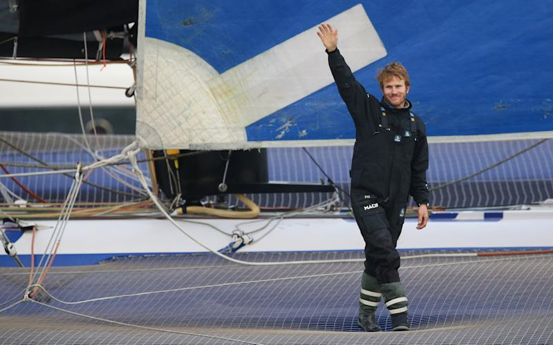 French skipper Francois Gabart celebrates as he sails the trimaran Macif into Brest harbour -  STEPHANE MAHE