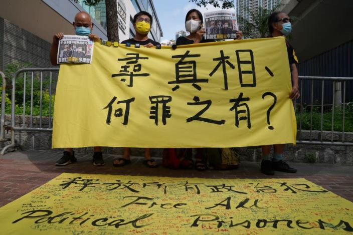 Supporters hold a copies of Apple Daily newspaper and a banner during a court hearing outside West Magistrates' Courts, after police charge two executives of the pro-democracy Apple Daily newspaper over the national security law, in Hong Kong