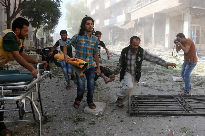 Rescuers and volunteers evacuate a wounded person following reported air strikes in the rebel-controlled neighbourhood of Saleheen of the northern Syrian city of Aleppo, in July 2016 (AFP Photo/Thaer Mohammed)