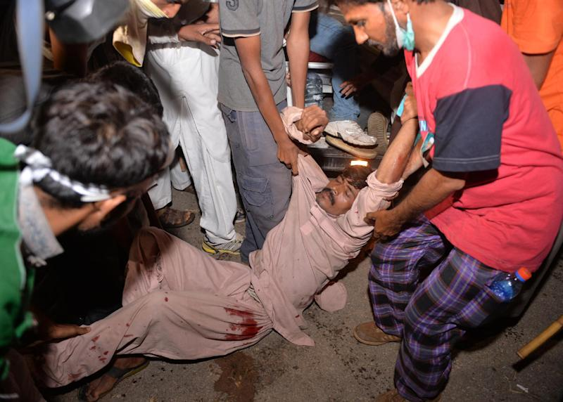 Opposition supporters carry a wounded protester following clashes with security forces near the prime minister's residence in Islamabad on August 30, 2014 (AFP Photo/Aamir Qureshi )
