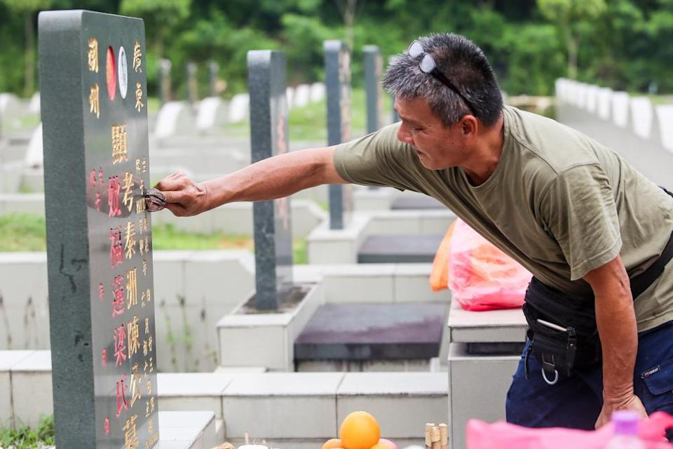 A man cleans the tombstone of a relative at Kwong Tong Cemetery in Kuala Lumpur. — File picture by Choo Choy May