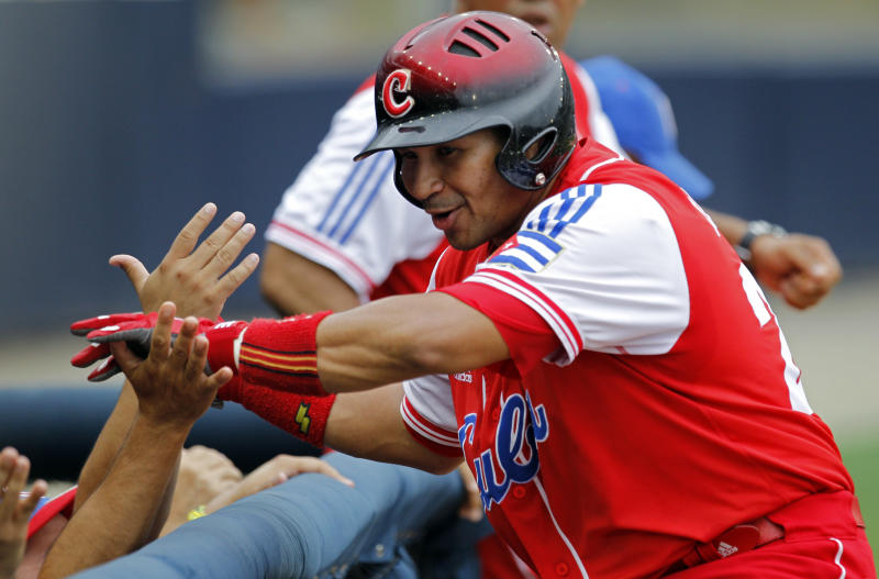 FILE - In this Oct. 14, 2011 file photo, Cuba's designated hitter Frederich Cepeda is congratulated by teammates after scoring during the third inning of their Baseball World Cup second round game against Canada in Panama City. One of the five top active players in Cuba's National Series, Cepeda is a switch-hitting terror who went .357 at the plate last season. Cuba on Friday, Sept. 27, 2013 announced that athletes from all sports will soon be able to ply their trade in foreign leagues. (AP Photo/Andres Leighton, File)