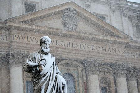 The statue of Saint Peter is pictured during a heavy snowfall in Saint Peter's Square at the Vatican. REUTERS/Max Rossi