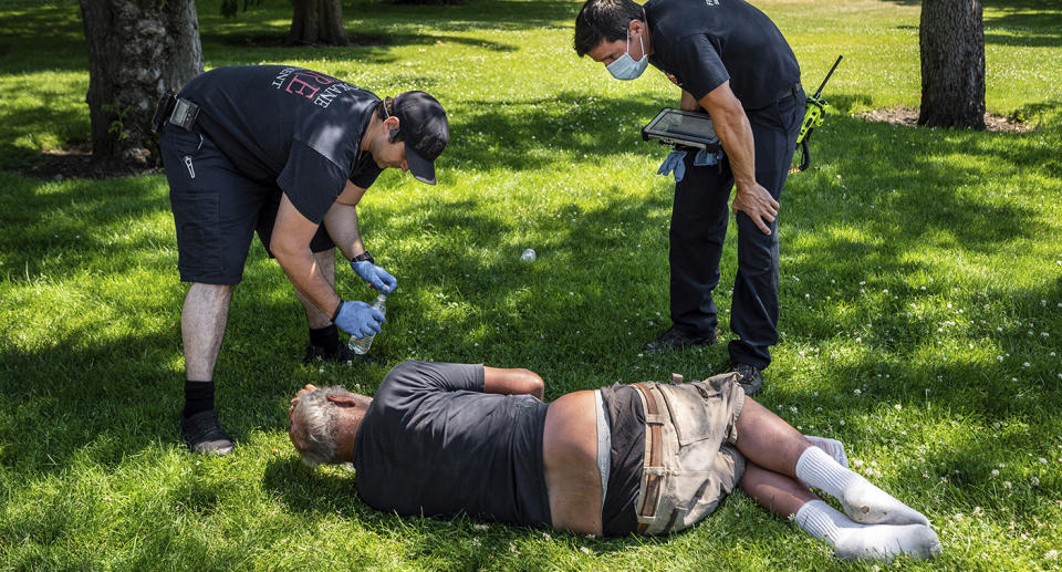 Man lies on grass and is assisted by paramedics.