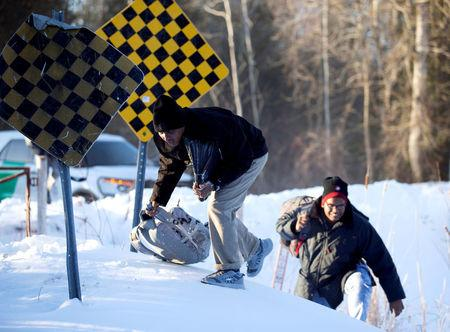 A man who claimed to be from Sudan climbs over a pile of snow as he and his family illegally cross the U.S.-Canada border leading into Hemmingford