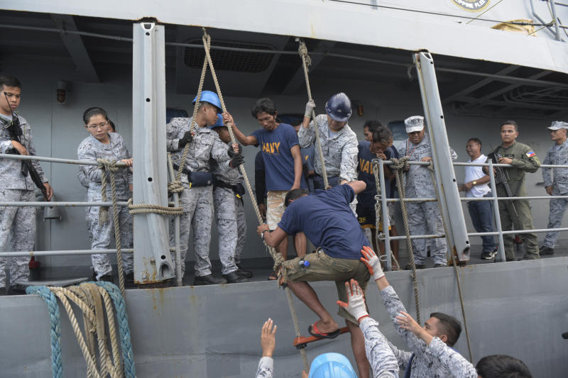 FILE - In this  June 14, 2019, file photo, rescued Filipino fishermen are transferred to another ship as they head back to shore in Occidental Mindoro province, Philippines, after sinking of their fishing boat by a Chinese trawler in the South China Sea. In a meeting of the Association of Southeast Asian Nations' defense chiefs, Philippine Defense Secretary Delfin Lorenzana thanked the Vietnamese captain whose boat rescued the 22 Filipino fishermen. (AP Photo, File)