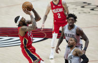 New Orleans Pelicans forward Brandon Ingram, left, shoots over Portland Trail Blazers guard Damian Lillard, bottom right, and forward Nassir Little during the first half of an NBA basketball game in Portland, Ore., Tuesday, March 16, 2021. (AP Photo/Craig Mitchelldyer)