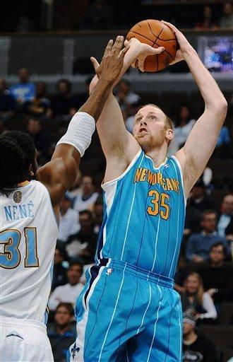 New Orleans center Chris Kaman, right, shoots over Denver Nuggets forward Nene, of Brazil, during the first quarter of an NBA basketball game Monday, Jan. 9, 2012, in Denver. (AP Photo/Chris Schneider)