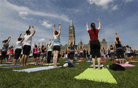 People take part in a free weekly yoga class on the front lawn of Parliament Hill in Ottawa
