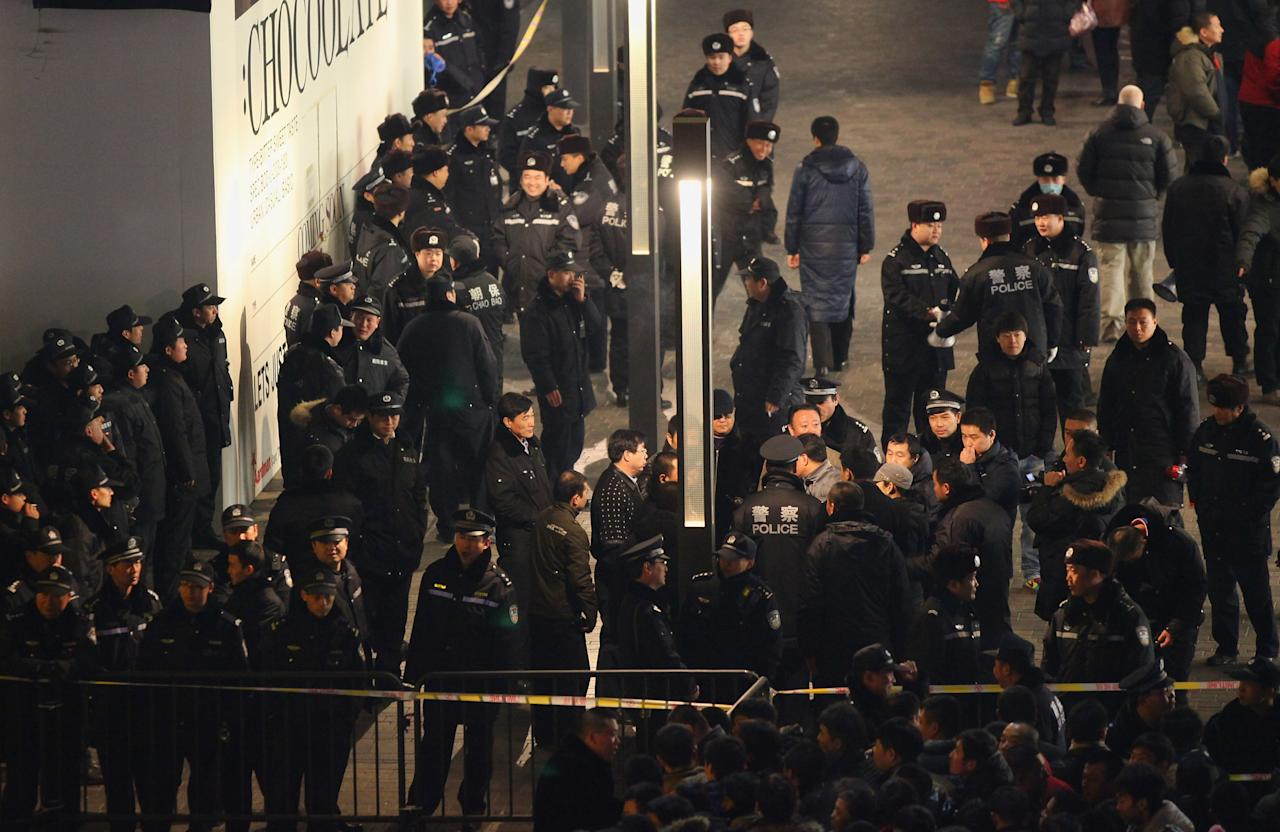 BEIJING, CHINA - JANUARY 13: Chinese policemen guard as people waiting outside an Apple store all night before the mainland release of iPhone 4S on January 13, 2012 in Beijing, China.  Apple recently announced iPhone 4S will be released in China and 21 other countries on January 13.  (Photo by Feng Li/Getty Images)