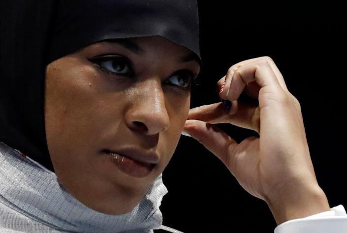 Ibtihaj Muhammad of the United States adjusts her hijab prior to competing in the women's individual saber fencing event at the 2016 Summer Olympics in Rio de Janeiro.