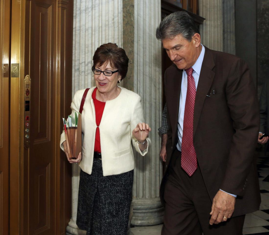 Senators Susan Collins (R-ME) and Joe Manchin (D-WV) walk into the Senate chamber to vote on the U.S. budget bill in Washington December 18, 2013. The U.S. Senate on Wednesday passed a two-year budget deal to ease automatic spending cuts and reduce the risk of another government shutdown, shifting the focus to a spending measure that Congress must pass by January 15. REUTERS/Gary Cameron (UNITED STATES - Tags: POLITICS BUSINESS)