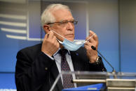 European Union foreign policy chief Josep Borrell takes off his protective face mask as he prepares to speak during a media conference after a meeting of EU foreign ministers at the European Council building in Brussels, Monday, Feb 22, 2021. (Johanna Geron, Pool via AP)