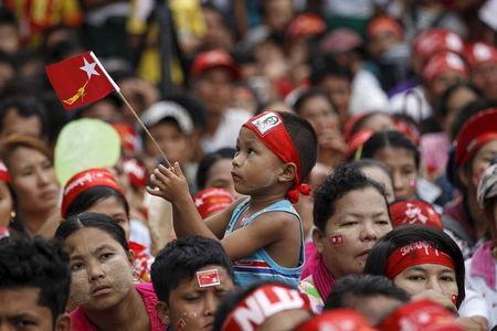 A boy holds a National League for Democracy (NLD) flag during a speech by Myanmar pro-democracy leader Aung San Suu Kyi as she campaigns in her constituency of Kawhmu township outside Yangon September 21, 2015. REUTERS/Soe Zeya Tun