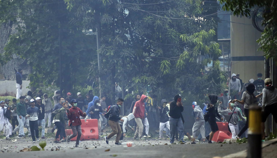 Student protester throws rock at riot police officers during a clash in Jakarta, Indonesia, Monday, Sept. 30, 2019. Thousands of Indonesian students resumed protests on Monday against a new law they say has crippled the country's anti-corruption agency, with some clashing with police.(AP Photo/Achmad Ibrahim)