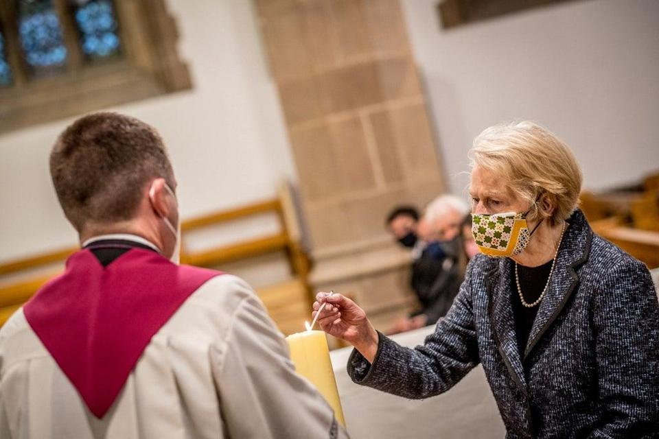 John Hume's wife, Pat, lights a candle as her husband's coffin is brought to St Eugene's Cathedral in Londonderry at his funeral last year (Peter Latimer/PA) (PA Archive)