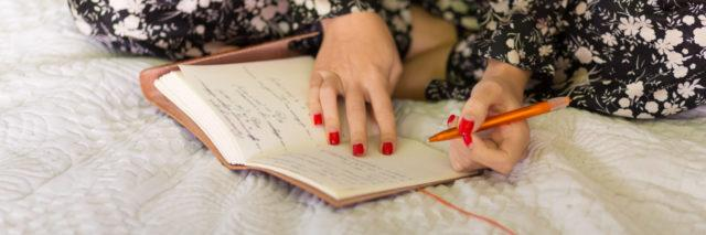 Woman writing in her diary in bed.