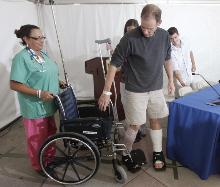 Christopher Myers, of Denver, gets into his wheelchair after a media availability at Massachusetts General Hospital after receiving treatment as the result of a shark attack in Boston, Friday, Aug. 3, 2012. Myers was bitten off Ballston Beach in Truro on Monday. (AP Photo/Stephan Savoia)