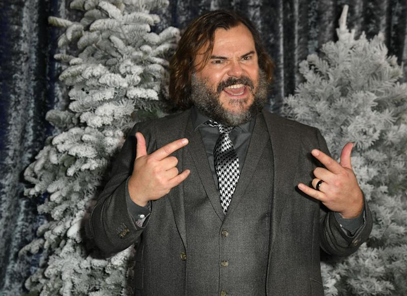 "Jack Black doing the ""Hook Em' Horns"" finger signs in a stylish way. He is also sporting a well tailored grey suit with black and white poaches tie to match"