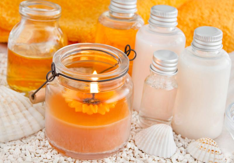 An orange candle sitting next to bottles of white lotion and seashells