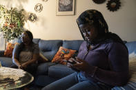 Fatumata Kromah, right, daughter of Rebecca Williams Sonyah, left, browses social media as her mother is interviewed at her home, Thursday, April 22, 2021, in Brooklyn Center. Minn. When protests began in a Minneapolis suburb after a white police officer fatally shot a Black man, 21-year-old Fatumata Kromah took to the street, pushing for change she says is essential to her Liberian immigrant community.(AP Photo/John Minchillo)