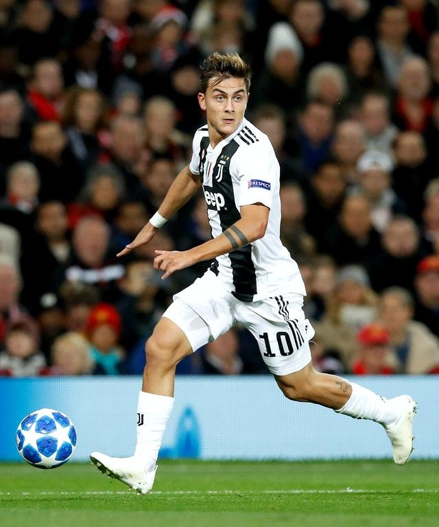 Paulo Dybala runs with the football in front of his right boot