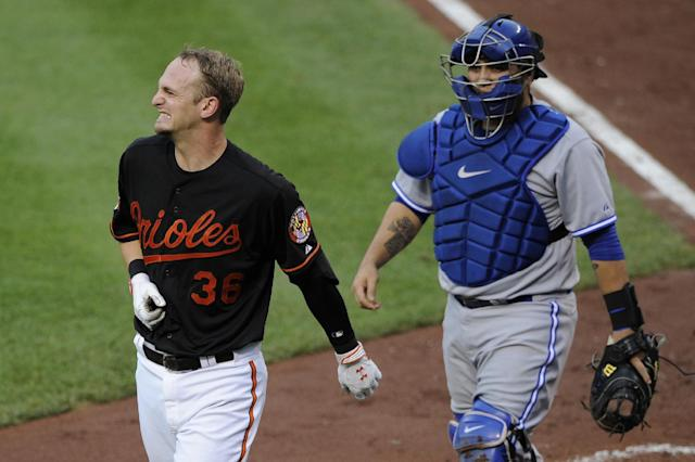 Baltimore Orioles' Caleb Joseph (36) reacts after he was hit by a pitch during the third inning of a baseball game as Toronto Blue Jays catcher Dioner Navarro looks on, Friday, June 13, 2014, in Baltimore. Joseph remained in the game. (AP Photo/Nick Wass)