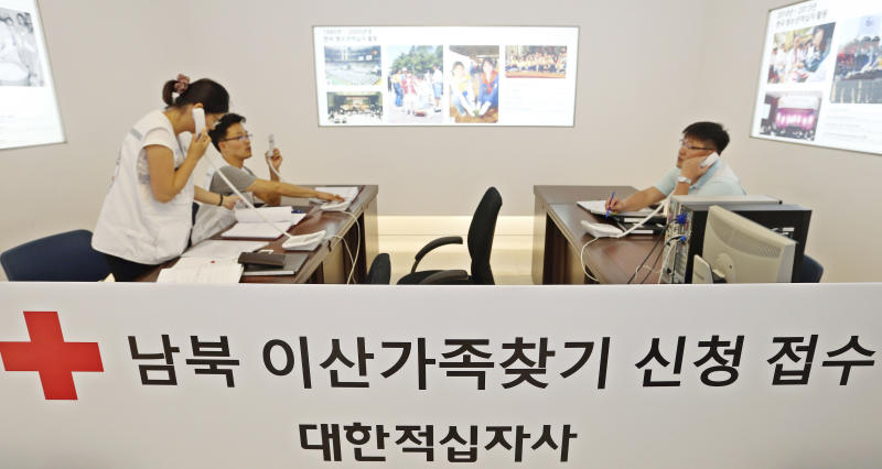 "Red Cross officials work at an office for reunion of families at the headquarters of the Korea Red Cross in Seoul, South Korea, Sunday, Aug. 18, 2013. North Korea on Sunday accepted South Korea's offer for talks on holding a reunion of families separated by war, but proposed separate talks on resuming jointly run tours in North Korea, implying it wants a restart of the lucrative tours in return for it allowing the reunions. The letters read ""South and North, Receive application for reunion of families."" (AP Photo/Han Jong-chan, Yonhap) KOREA OUT"