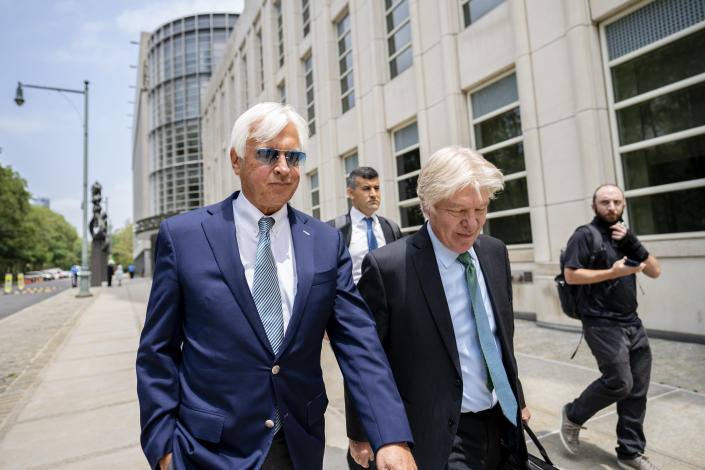 FILE - In this Monday, July 12, 2021 file photo, Horse trainer Bob Baffert, left, leaves federal court in the Brooklyn borough of New York. A New York federal judge on Wednesday, July 14, 2021 nullified the suspension of horse trainer Bob Baffert, finding that the New York Racing Association acted unconstitutionally by failing to let him adequately respond to claims made against him after Kentucky Derby winner Medina Spirit failed a postrace drug test.(AP Photo/John Minchillo, File)