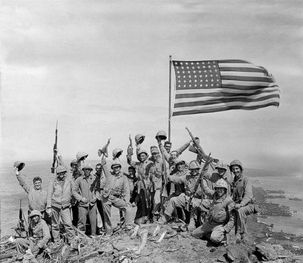 PHOTO: U.S. Marines of the 28th Regiment, fifth division, cheer and hold up their rifles after the second flag raising atop Mount Suribachi on Iwo Jima, a volcanic Japanese island, on Feb. 23, 1945 during World War II. (Joe Rosenthal/AP)