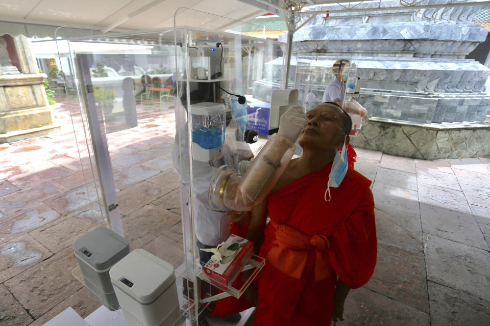 Health workers collect a nasal swab sample from a Buddhist monk to test for the coronavirus at the Wat Pho temple in Bangkok, Thailand, Saturday, May 30, 2020. (AP Photo/Sarayuth Jojaiharn)