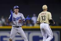 Los Angeles Dodgers' Andy Burns (29) celebrates his double against the Arizona Diamondbacks as Diamondbacks shortstop Nick Ahmed (13) waits for a late throw during the eighth inning of a baseball game Friday, June 18, 2021, in Phoenix. The Dodgers won 3-0. (AP Photo/Ross D. Franklin)