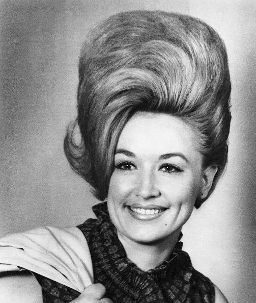 <p>Dolly Parton always had big hair—even before she was a blonde. In 1965, the future country star posed in a photograph where she sported this elaborate comb-over bouffant. </p>